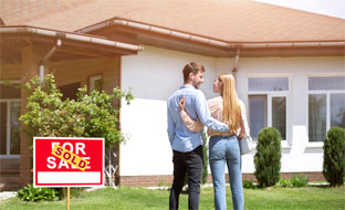 A newlywed couple standing in the front yard of their new residential property.